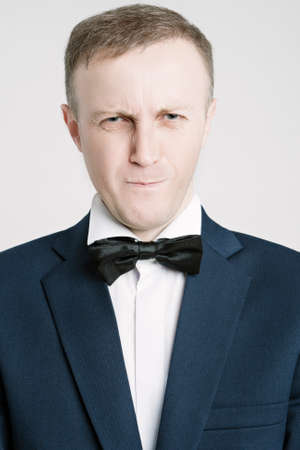 against white: Portrait of Caucasian Handsome Man in Blue Suite Making Faces. Posing Against White. Vertical Image Stock Photo