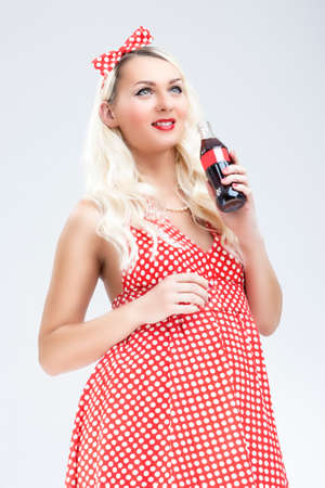 charm temptation: Pinup and Retro Concepts. Sexy Caucasian Pinup Blond Woman With Drink Bottle Posing in Polka Dotted Dress Against White.Vertical Image