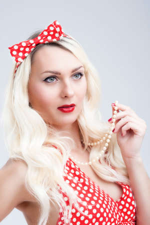 charm temptation: Pinup Style and Concepts. Sexy Sensual Caucasian Blond Woman in Red Polka Dotted Dress. Posing Against White, Vertical Shot