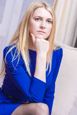 light hair: Thoughtful Blond Caucasian Woman in Blue Dress Sitting on Couch Indoors. Vertical Image Composition Stock Photo