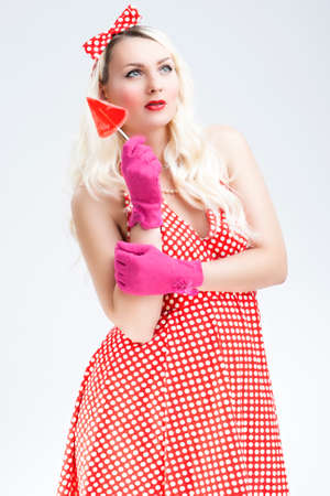 against white: Pinup Caucasian Blond Woman With Red Sweet Candy.Posing Against White Background. Vertical Image Stock Photo