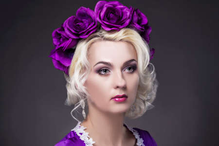 charm temptation: Beauty Concepts. Closeup Portrait of Caucasian Blond Female Model In Purple Dress with Violet Flowery Crown.Horizontal Image