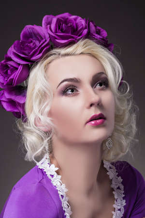 flowery: Beauty Concept and Ideas. Caucasian Female Posing in Purple Dress with Flowery Violet Crown. Vertical Image Composition Stock Photo