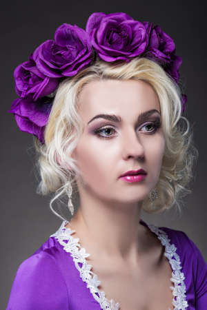 charm temptation: Beauty Concepts. Closeup Portrait of Caucasian Blond Female Model In Purple Dress with Violet Flowery Crown.Vertical Image