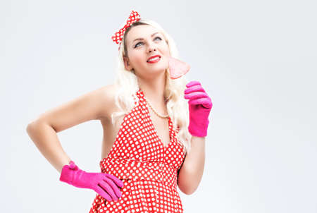 charm temptation: Pinup Retro Concepts. Dreaming Sensual Pinup Blond Woman With Sweet Candy Posing in Polka Dotted Dress on White. Horizontal Image Composition