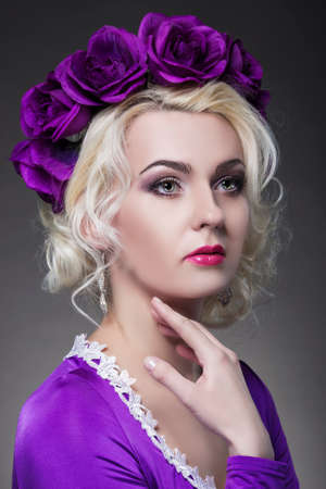charm temptation: Beauty and Fashion Concept and Ideas. Blond Caucasian Female Posing in Purple Dress. Crowned with Flowery Violet Crown. Vertical Image