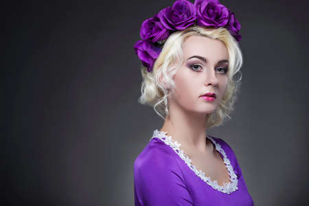 Beauty and Fashion Concept and Ideas. Blond Caucasian Female Posing in Purple Dress. Crowned with Flowery Violet Crown. Against Black