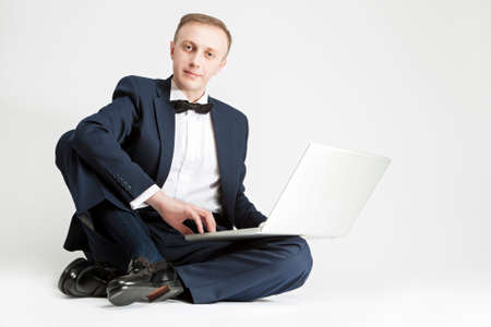 against white: Portrait of Handsome Caucasian Man in Suit with Laptop. Sitting on Floor. Against White Background. Horizontal Image Stock Photo