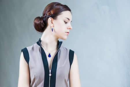 pendent: Portrait of Sensual Brunette Female with Blue  Pendent and Earring Against Gray Wall. Horizontal Image