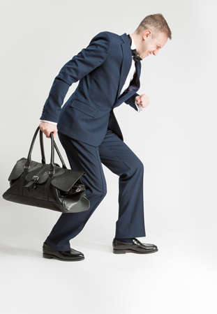 hauling: Humorous Concept and Ideas. Handsome Caucasian Man in Official Suit and Bow Tie Hauling Leather Long Bag.Vertical Shot Stock Photo