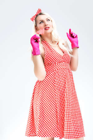 charm temptation: Pinup Retro Concepts. Dreaming Sexy Pinup Blond Woman With Sweet Candy Posing in Polka Dotted Dress on White. Vertical Image Composition