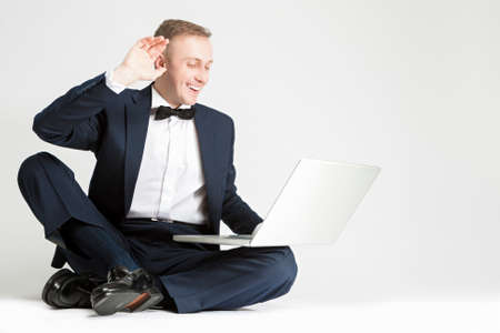 against white: Happy Smiling Caucasian Man in Blue Suit with Laptop Chatting and Showing High Five. Sitting on Floor. Against White Background. Horizontal Image