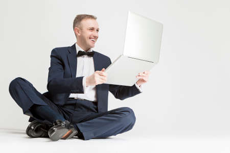 against white: Young Smiling Caucasian Blond Man Holding  Laptop and Smiling. Sitting Against White. Horizontal Image