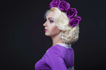 charm temptation: Fashion and Beauty Concepts. Portrait of Blond Caucasian Female With Purple Flowery Crown Posing Against Black.Horizontal Image