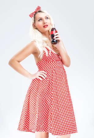 polka dotted: Retro Concepts. Sexy Pinup Blond Woman With Drink Bottle Posing in Polka Dotted Dress. Vertical Image Stock Photo