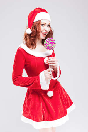 sugarplum: Portrait of Alluring Caucasian Red haired Santa Helper with Color Sweet Lollipop Sugar-Plum Candy. Vertical Image