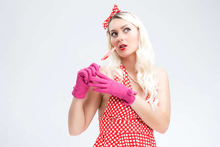 against white: Sexy Flirting Pinup Caucasian Blond Woman With Red Sweet Candy.Posing Against White Background.Horizontal Image