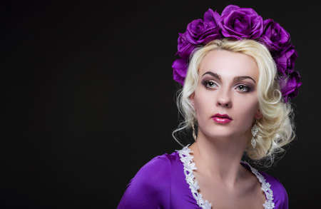 flowery: Fashion and Beauty Concepts. Portrait of Blond Caucasian Female With Purple Flowery Crown Against Black.Horizontal Image