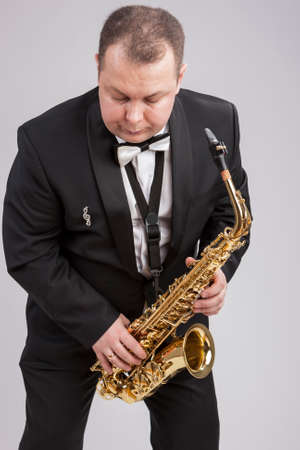man in suite: Caucasian Man in Suite with Saxophone. Posing Against White. Vertical Image