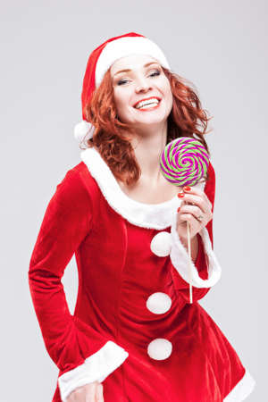 sugarplum: Happy Alluring Caucasian Red haired Santa Helper with Color Sweet Lollipop Sugar-Plum Candy. Vertical Image