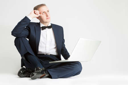 against white: Portrait of Thinking Caucasian Man in Suit with Laptop. Sitting on Floor. Against White Background. Horizontal Image Stock Photo