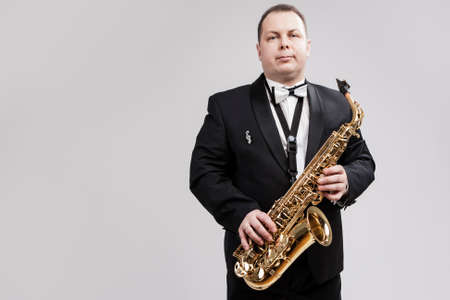 man in suite: Man with Saxophone in Suite Posing Against White Background. Horizontal Image Orientation