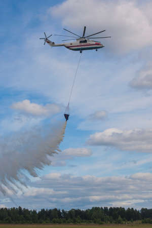 80th: Minsk, Belarus-June 21, 2014: Staff of Ministry of Emergency Situations Spraying Water over Trees on MI-26 Helicopter During Aviation Sport Event Dedicated to the 80th Anniversary of DOSAAF Foundation in Minsk on June 21, 2014 in Minsk, Belarus