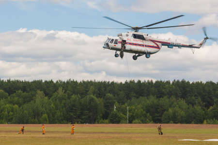 situations: Minsk, Belarus-June 21, 2014: Staff of Ministry of Emergency Situations Spraying Water over Trees on MI-8MT Helicopter During Aviation Sport Event Dedicated to the 80th Anniversary of DOSAAF Foundation in Minsk on June 21, 2014 in Minsk, Belarus