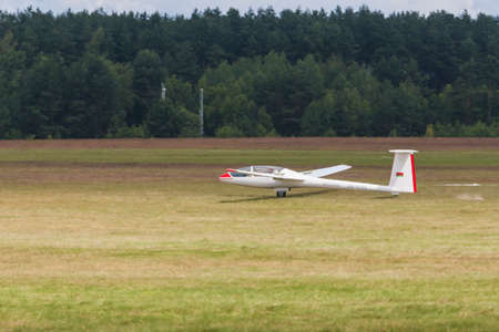 landing strip: Minsk, Belarus-June 21, 2014: Glider on Takeoff and Landing Strip During Aviation Sport Event Dedicated to the 80th Anniversary of DOSAAF Foundation in Minsk on June 21, 2014 in Minsk, Republic of Belarus