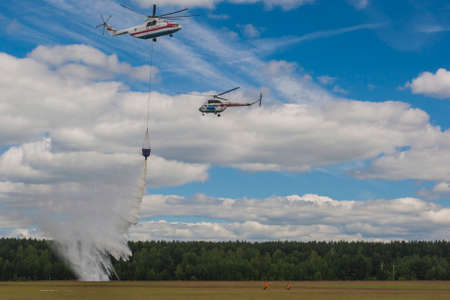 situations: Minsk, Belarus-June 21, 2014: Staff of Ministry of Emergency Situations Spraying Water over Trees on MI-8 and MI-26 Helicopters During Aviation Sport Event Dedicated to the 80th Anniversary of DOSAAF Foundation in Minsk on June 21, 2014 in Minsk, Belarus
