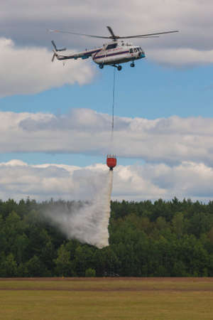 situations: Minsk, Belarus-June 21, 2014: Staff of Ministry of Emergency Situations Spraying Water over Trees on MI-8 Helicopter During Aviation Sport Event Dedicated to the 80th Anniversary of DOSAAF Foundation in Minsk on June 21, 2014 in Minsk, Belarus