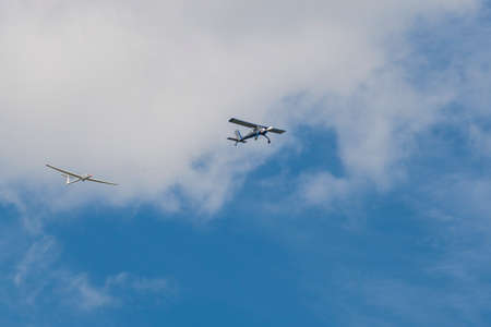 80th: Minsk, Belarus-June 21, 2014: Two Airplanes of Glider and Aircraft on Coupling Performing Elements in Air In Front of Spectators During Aviation Sport Event Dedicated to the 80th Anniversary of DOSAAF Foundation in Minsk on June 21, 2014 in Minsk, Republi