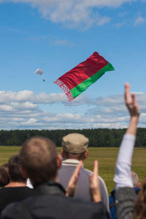 80th: Minsk, Belarus-June 21, 2014: International Parachuter�s Team Performing in Air While Unwinding National Flag of the Republic of Belarus In Front of Spectators During Aviation Sport Event Dedicated to the 80th Anniversary of DOSAAF Foundation in Mi Editorial