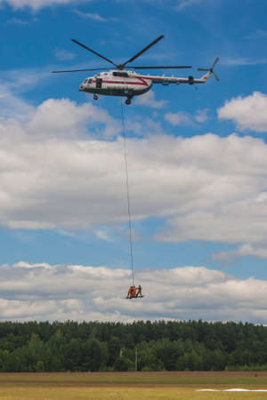 situations: Minsk, Belarus-June 21, 2014: Staff of Ministry of Emergency Situations Performing Air Elements on MI-8MT Helicopter During Aviation Sport Event Dedicated to the 80th Anniversary of DOSAAF Foundation in Minsk on June 21, 2014 in Minsk, Republic of Belarus