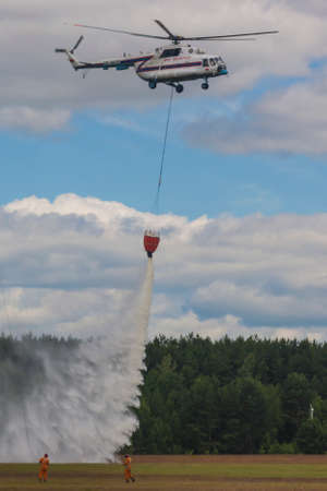 80th: Minsk, Belarus-June 21, 2014: Staff of Ministry of Emergency Situations Spraying Water over Trees on MI-8 Helicopter During Aviation Sport Event Dedicated to the 80th Anniversary of DOSAAF Foundation in Minsk on June 21, 2014 in Minsk, Belarus