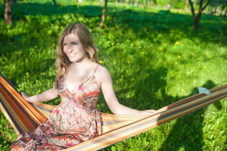 hummock: Portrait of Happy Smiling Blond Female Resting in Hummock in Spring Forest Outdoors.Horizontal Image