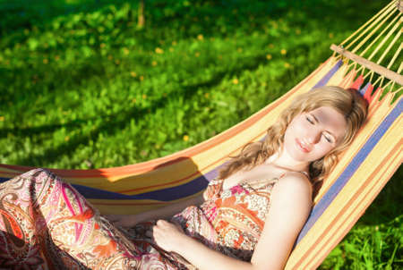 hummock: Cute Relaxing Caucasian Lady Resting in Hummock and Dreaming Outdoors.Horizontal  Shot Stock Photo