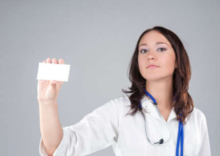 medico: Portrait of Medical Female Doctor Presenting and Showing White Card for Product or Text. Caucasian Medical Professional Staff Posing Against Gray.Focus on Card. Horizontal Image