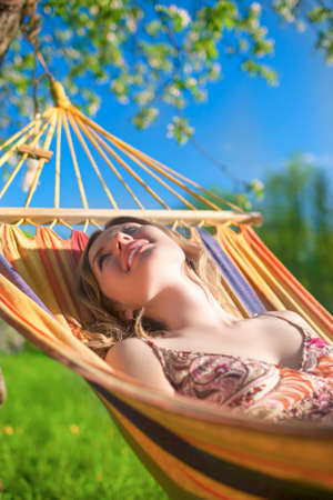 hummock: Portrait of Caucasian Blond Lady Resting in Hummock During Spring Time Outdoors.Vertical Image Composition Stock Photo