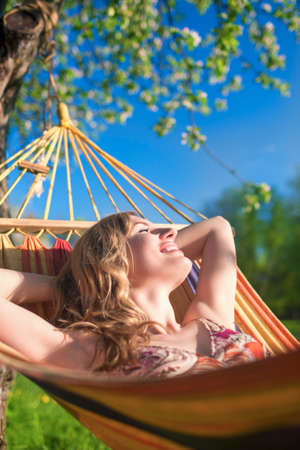 hummock: Portrait of Smiling Caucasian Blond Lady Resting in Hummock During Spring Time Outdoors.Vertical Shot Stock Photo