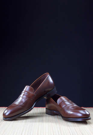 loafer: Shoes concepts. Mens Brown Stylish Penny Loafer Shoes On Straw Surface Against Black Background. Vertical Image