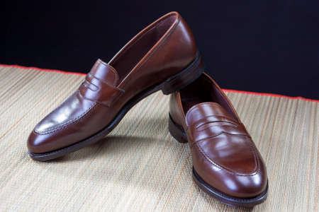 loafer: Mens Footwear Concepts. Pair of Stylish Brown Penny Loafer Shoes Placed on Straw Surface against Black.Horizontal Image