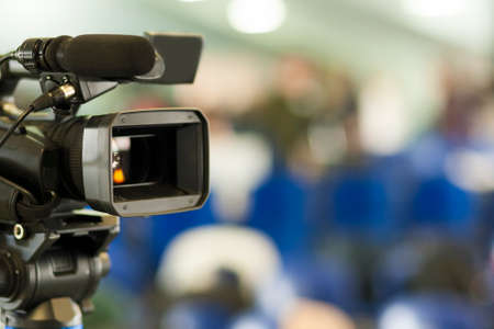 Front View of Professional Videocamera. Positioned Against Blurred Background. Horizontal Image Stock Photo