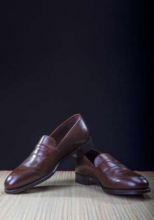 loafer: Mens Brown Penny Loafer Shoes Against Black Background. Vertical Image Composition Stock Photo