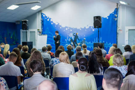 Female Leader Lecturer Speaking In front of the Large Group of People. Horizontal Image Composition