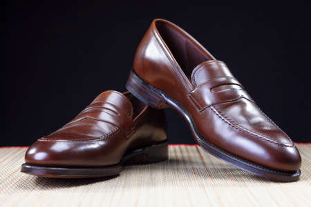 loafer: Footwear Concepts. Pair of Stylish Brown Penny Loafer Shoes Placed on Straw Surface against Black.Horizontal Shot