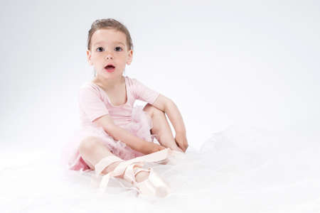 pointes: Cute Little Kid Posing as Ballerina. Putting Pointes on. Against White Background. Horizontal Image Composition Stock Photo