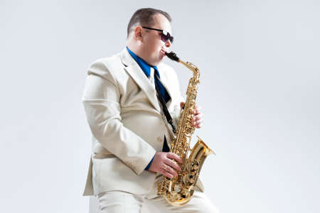 Portrait of Expressive Stylish Caucasian Saxophone Player Performing in White Suit and Sunglasses in Studio. Horizontal Image Orientation