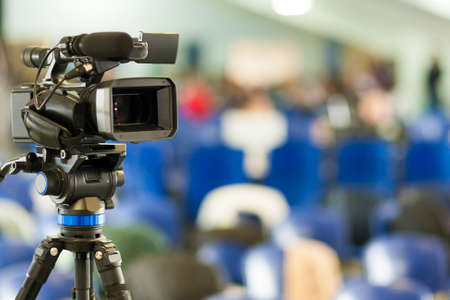positioned: Front View of Professional Videocamera. Positioned Against Blurred Background. Horizontal Image Stock Photo