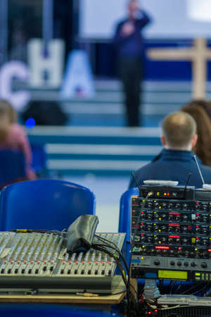 decibels: Closeup of Professional Mixing Console During Conference. With the Blurred Silhouette of  Spokesperson on a Background. Vertical Image Stock Photo